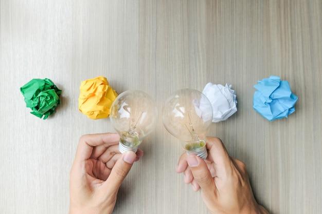 Mão segurando a lâmpada ou lâmpada com papel amassado colorido
