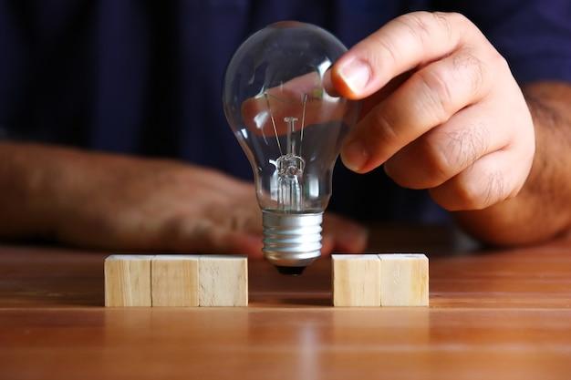 Mão segurando a lâmpada substituindo o bloco de madeira no piso de madeira, conceito de ideia