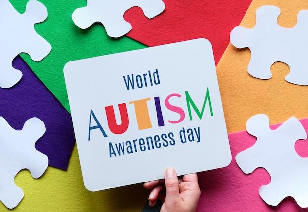 Mão segurando a legenda para o dia mundial da conscientização sobre o transtorno do espectro do autismo