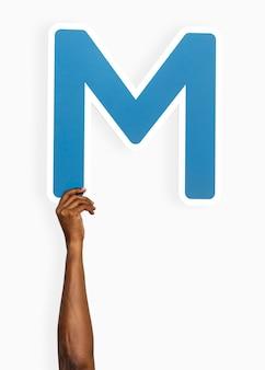 Mão segurando a letra m