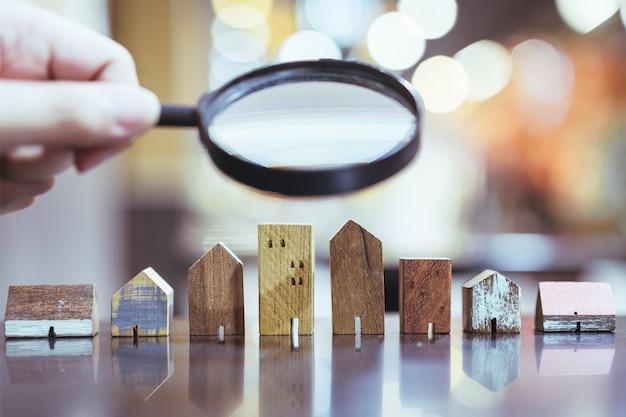 Mão segurando a lupa e olhando para o modelo de casa