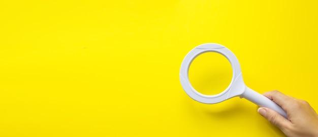 Mão segurando a lupa em amarelo. análise e estatísticas de negócios.