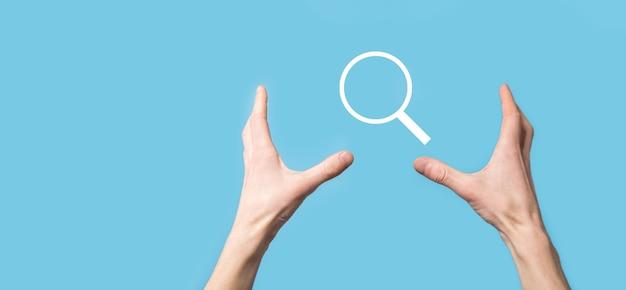 Mão segurando a lupa, ícone de pesquisa sobre fundo azul. otimização do motor de busca de conceito