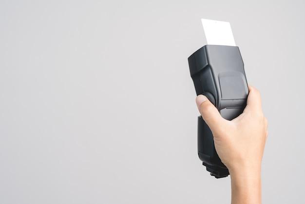 Mão segurando a luz da velocidade do flash externo da câmera