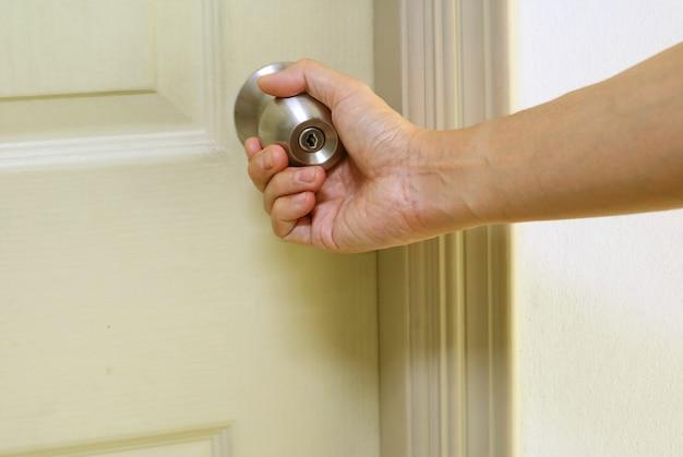 Mão segurando a maçaneta de aço, fechando a porta