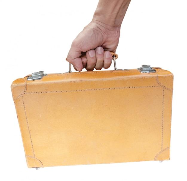 Mão segurando a mala marrom vintage isolada no fundo branco