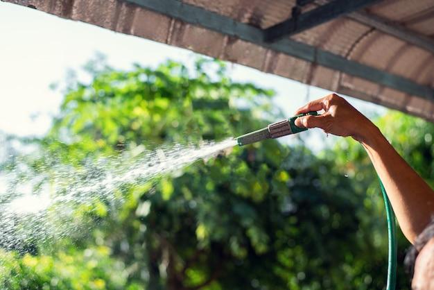 Mão segurando a mangueira de lavagem de carro