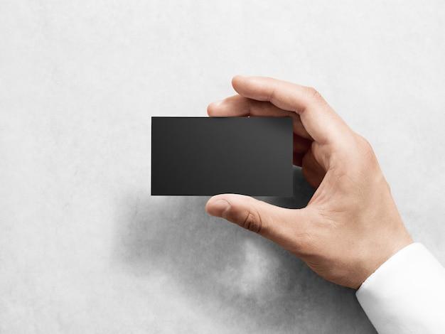 Mão segurando a maquete de design de cartão de visita preto simples em branco