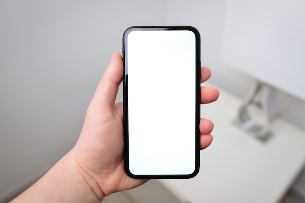 Mão segurando a maquete de smartphone preto com tela grande em branco visor sem moldura no telefone tecnologia moderna na mão do homem mão isolada em um fundo branco simule em branco de seu design