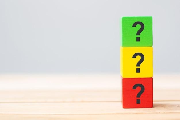 Mão segurando a marca de perguntas (?) no bloco de cubos de madeira no fundo da mesa. faq (perguntas frequentes), respostas, perguntas e respostas, conceitos de informação, comunicação e interrogatório