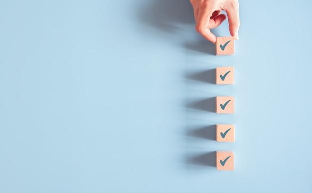Mão segurando a marca de seleção na superfície azul