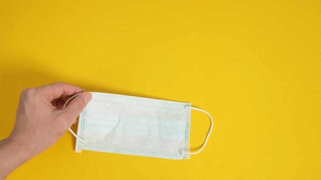 Mão segurando a máscara facial ou cirúrgica para proteção contra infecção de vírus e produtos químicos. coloque um fundo amarelo.