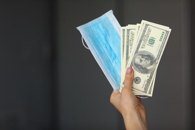 Mão segurando a máscara protetora de medicamento com notas de dólares. conceito de 19 quarentena de coronavírus. foco seletivo