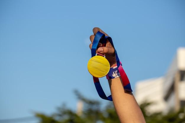Mão segurando a medalha ao ar livre