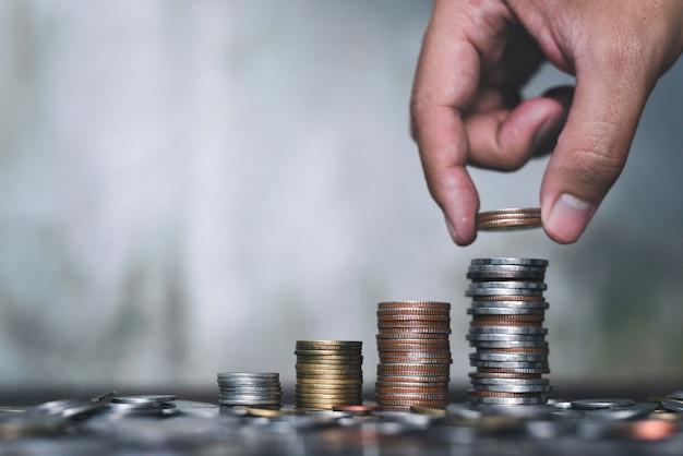 Mão segurando a moeda e pilha crescendo