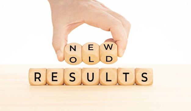 Mão segurando a palavra de resultados novo vs antigo em blocos de madeira na mesa. fundo branco. copie o espaço
