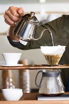 Mão segurando a panela, derramando água quente para o café pingando