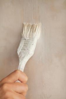 Mão segurando a parede de pintura a pincel. reparar