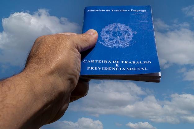 Mão segurando a pasta de trabalho brasileira no céu com nuvens.