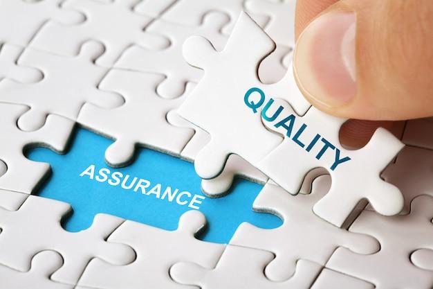 Mão segurando a peça do quebra-cabeça com a palavra garantia de qualidade. imagem do conceito de negócios
