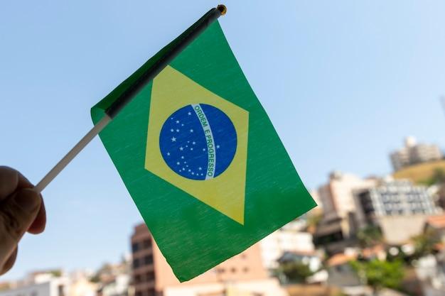 Mão segurando a pequena bandeira do brasil. ordem e progresso em português. bandeira brasileira