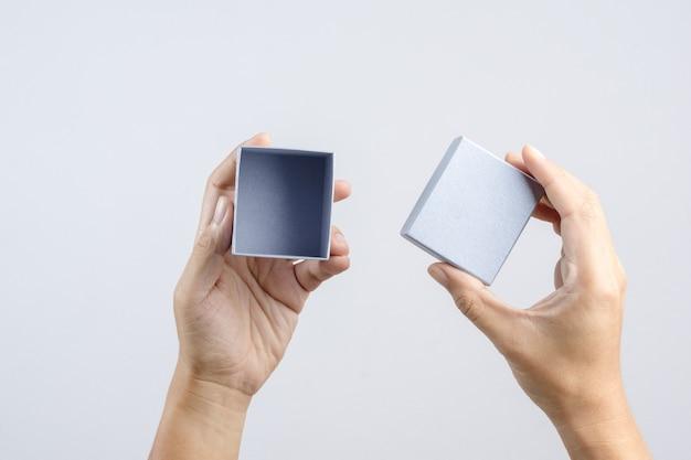 Mão segurando a pequena caixa de presente de luxo prata para ocasião especial