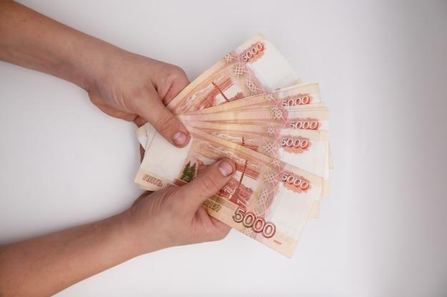 Mão segurando a pilha de rublos russos.