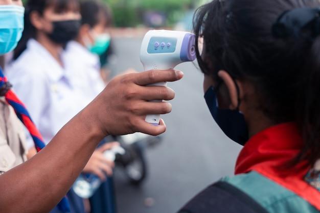 Mão segurando a pistola de termômetro infravermelho para teste de temperatura na testa