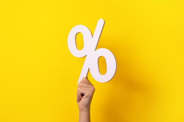Mão segurando a placa de porcentagem sobre fundo amarelo
