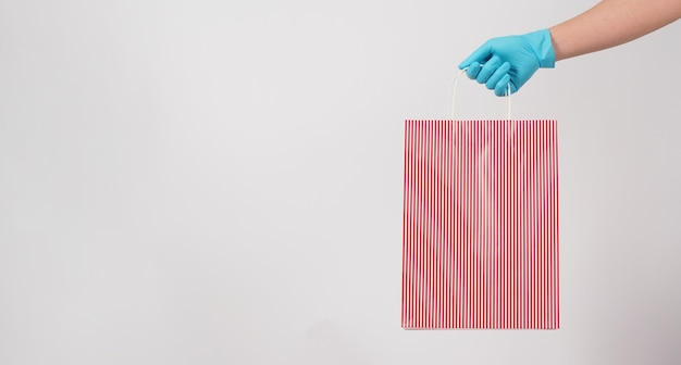 Mão segurando a sacola de compras de listras vermelhas e usar uma luva médica azul, isolada no fundo branco.