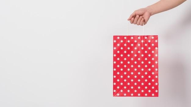 Mão segurando a sacola de compras padrão de estrela vermelha no espaço branco background.copy.