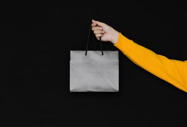Mão segurando a sacola de compras preta sobre fundo escuro. conceito de black friday.