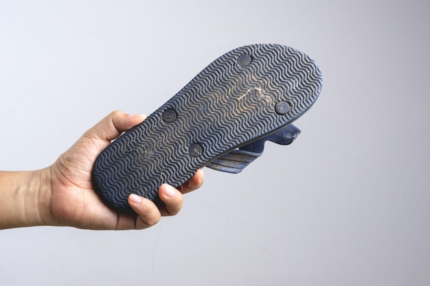 Mão segurando a sandália velha e suja como uma arma para matar um inseto