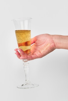 Mão segurando a taça de champanhe