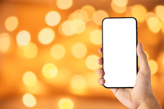 Mão segurando a tela em branco do smartphone em fundo amarelo ouro bokeh