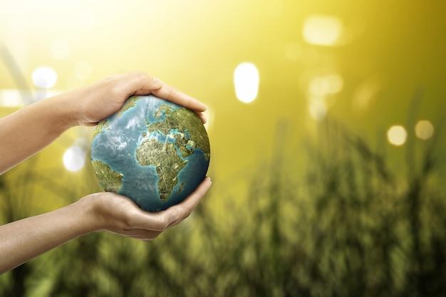 Mão segurando a terra com superfície de luz turva. dia mundial do meio ambiente