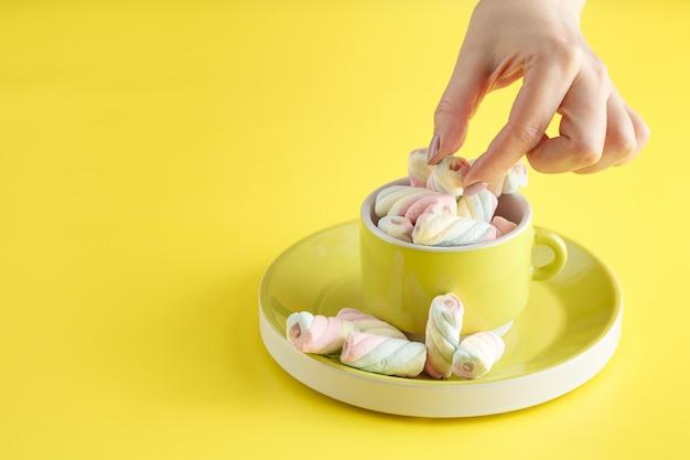 Mão segurando a tigela de doce marshmallow pastel isolada em fundo amarelo.