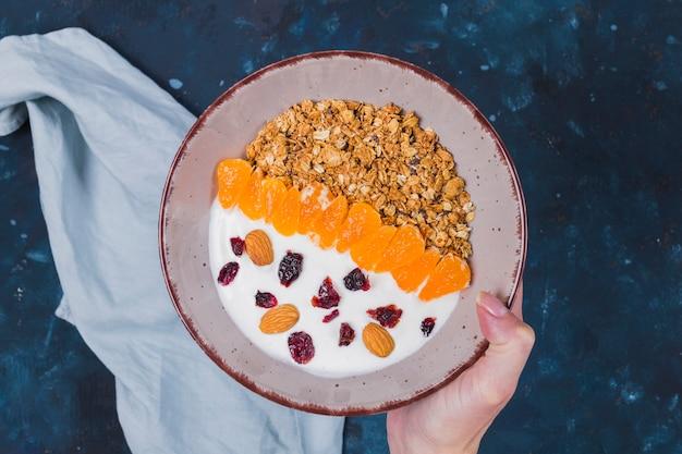 Mão segurando a tigela de frutas granola