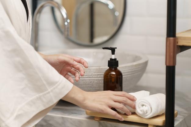 Mão segurando a toalha na pia do banheiro.