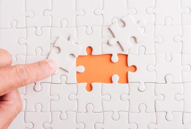 Mão segurando a última peça do jogo de quebra-cabeça