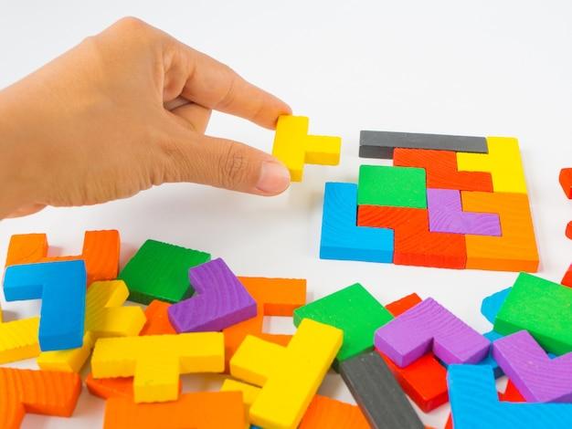 Mão segurando a última peça para completar um puzzle de madeira colorido quebra-cabeça tangram quadrado