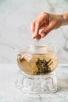 Mão segurando a vista frontal da tampa do bule de chá