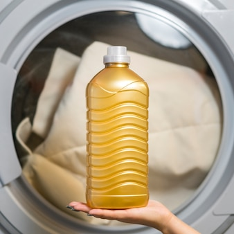 Mão segurando a vista frontal do frasco de detergente
