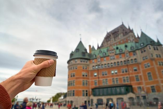 Mão segurando a xícara de café na cidade de quebec. close-up e foco seletivo
