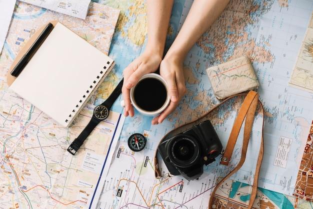 Mão segurando a xícara de café no mapa rodeado com o bloco de notas em espiral; bússola; relógio de pulso; câmera e cinta