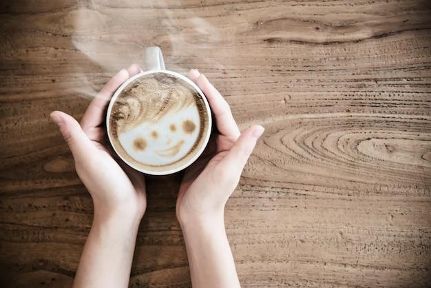 Mão segurando a xícara de café quente - pessoas com o conceito de café