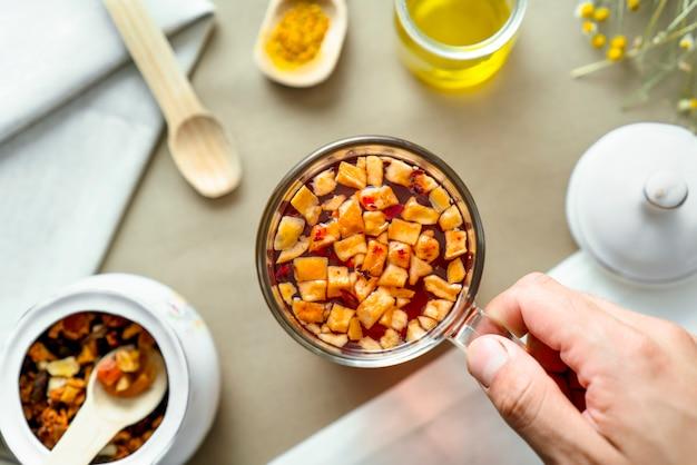 Mão segurando a xícara de chá de ervas na mesa