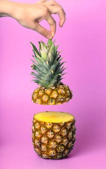 Mão segurando abacaxi em um fundo colorido em branco suco de vitaminas de frutas tropicais