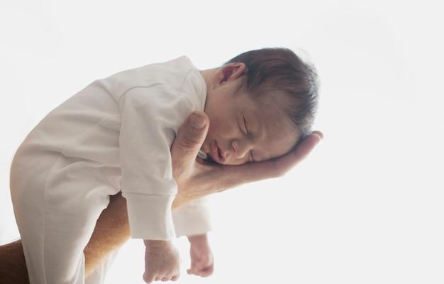 Mão segurando adorável recém-nascido