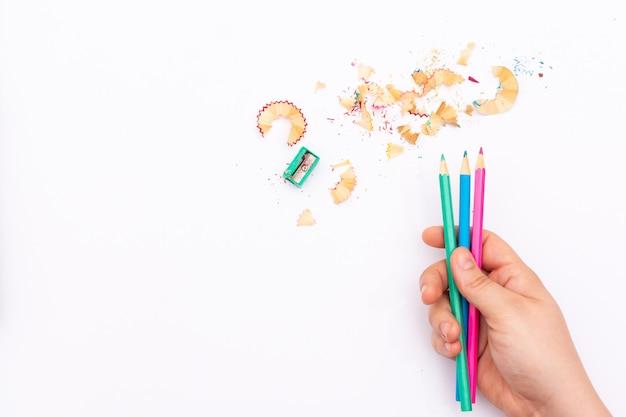 Mão segurando alguns lápis de cor sobre um fundo branco